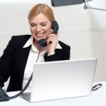 businesswoman on phone with computer by stockimages